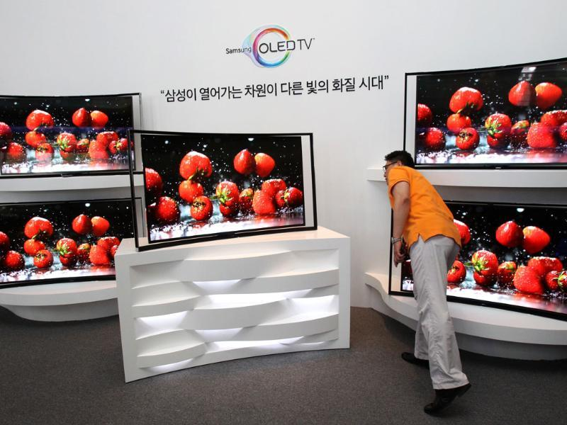 A journalist takes a close look at a Samsung Electronics Co.'s 55-inch curved OLED TV during a press conference at its headquarters in Seoul. Photo: AP/Ahn Young-joon