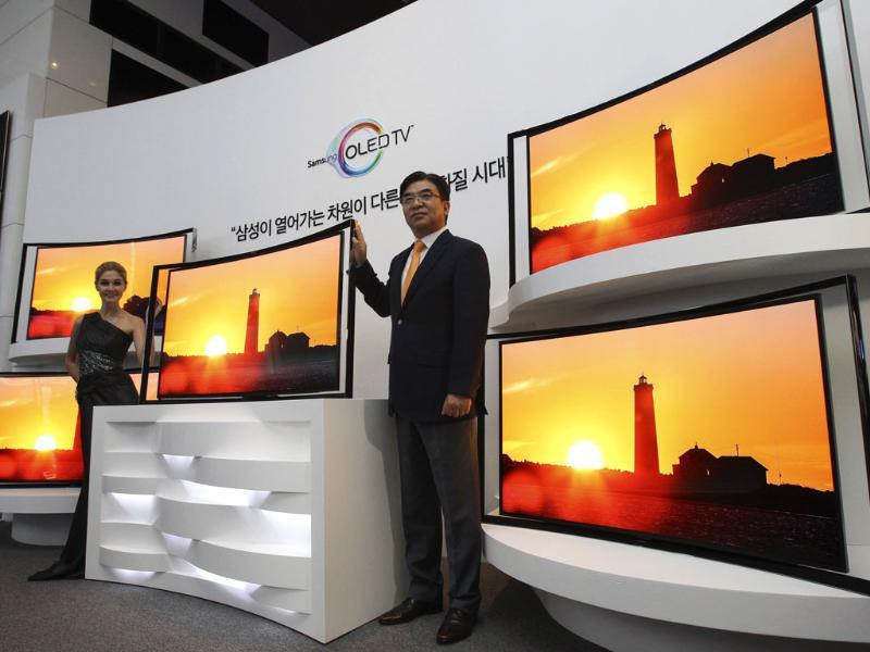 Kim Hyunsuk, the executive vice president of Samsung Electronics Co.'s TV division, right, poses with its 55-inch curved OLED TV during a press conference in Seoul. Photo:AP/Ahn Young-joon