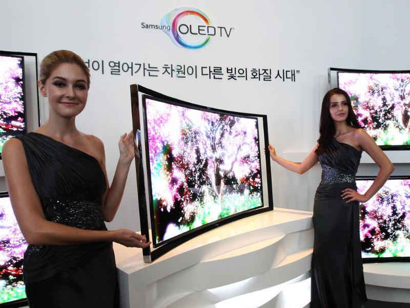 Models pose with a Samsung Electronics Co.'s 55-inch curved OLED TV during a press conference at its headquarters in Seoul. Photo: AP/Ahn Young-joon
