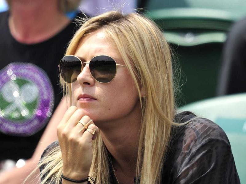 Maria Sharapova sits in the crowd watching the action between Bulgaria's Grigor Dimitrov and Slovakia's Grega Zemlja during their second round men's singles match on day four of the 2013 Wimbledon Championships tennis tournament at the All England Club in Wimbledon, southwest London. AFP Photo