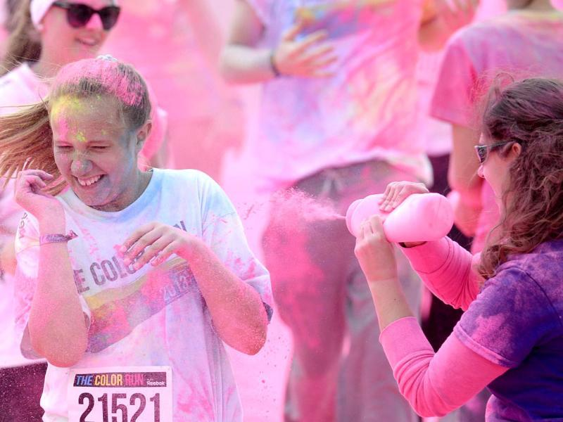 Participants of 'The Color Run' festival in Munich react as they get a colored powder shower at the pink zone during the event. AFP Photo