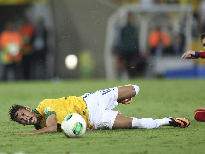 Brazil's Neymar falls after being fouled by Spain's Gerard Pique during the Confederations Cup final match at the Maracana stadium in Rio de Janeiro, Brazil. AP