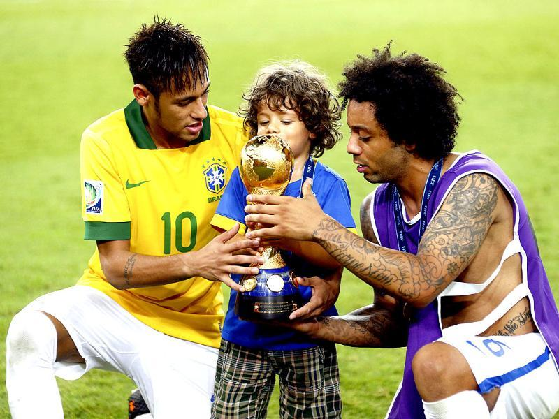 Brazil's Marcelo with his son hold the trophy as teammate Neymar celebrate winning their Confederations Cup final match against Spain at the Estadio Maracana in Rio de Janeiro. Reuters