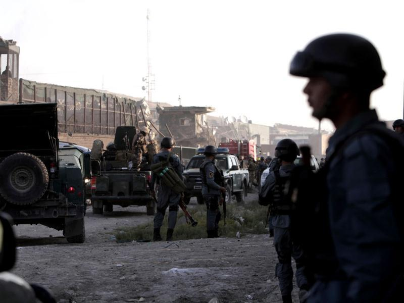 Afghan security officers stand at the entrance gate to a NATO compound in Kabul, Afghanistan after militants blew up a suicide car bomb at the gate. (AP Photo)