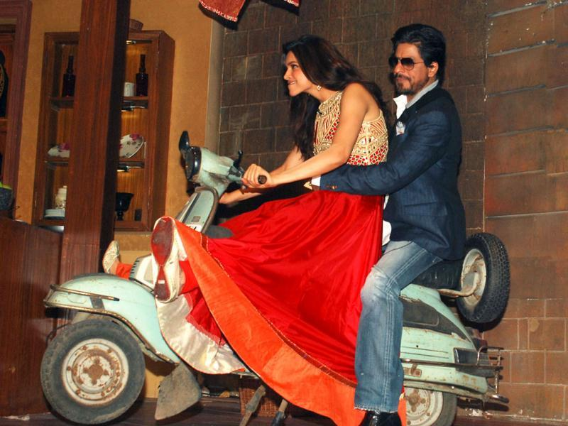 As Deepika gears up and bites her lips in excitement, Shah Rukh Khan looks a tad worried he may fall off as he 'pillion rides' on the fossilised scooter. (AFP Photo)