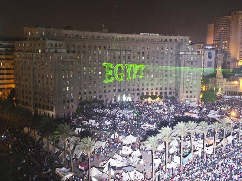 Egyptian protesters calling for the ouster of President Mohamed Morsi gather in Cairo's landmark Tahrir Square as laser lights (L) directed at the government building spell