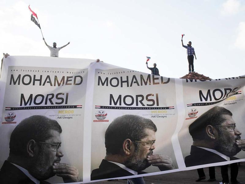 Supporters of President Mohamed Morsi carry a banner with his pictures during a protest to counter anti-Mursi protests elsewhere in Alexandria. (Reuters)