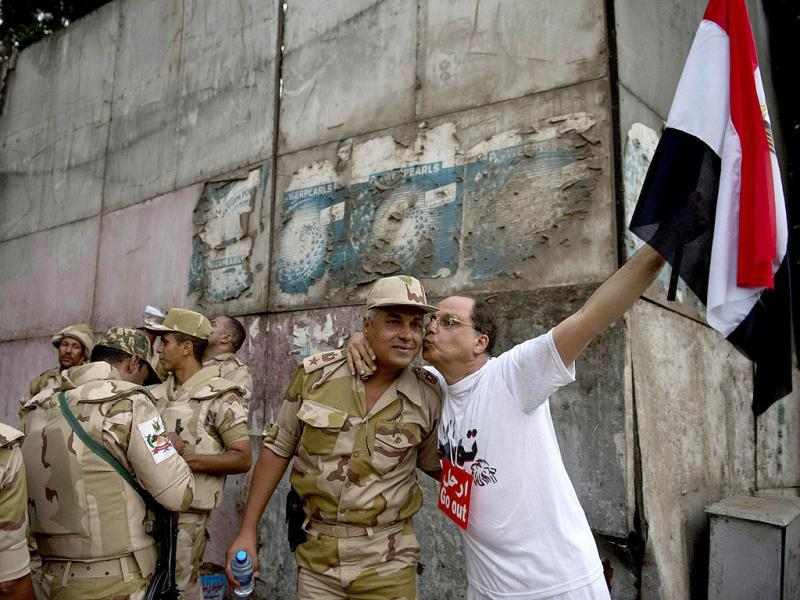 An Egyptian man welcomes an army soldier upon his deployment on a street leading to Cairo University. (AFP)