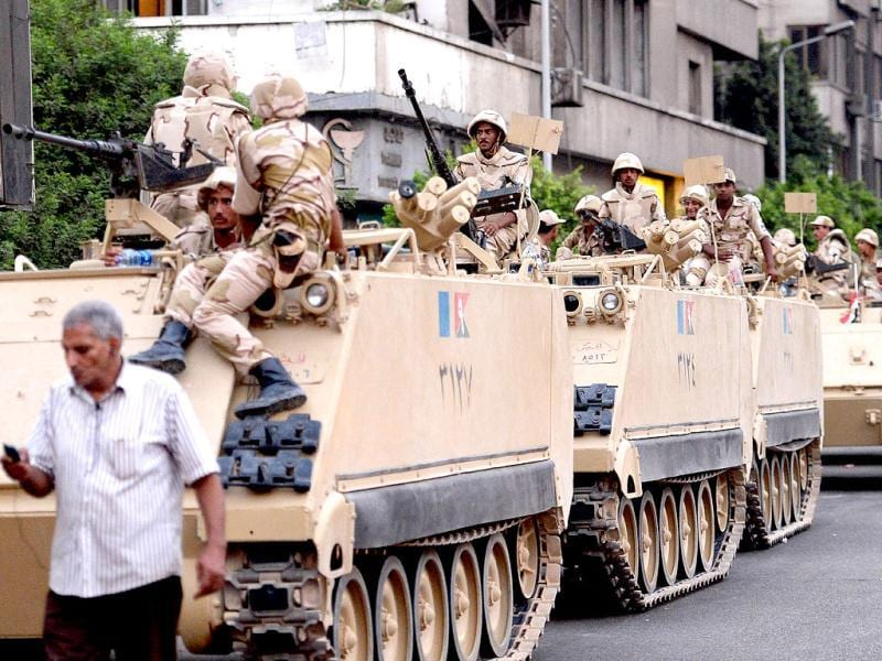 Egyptian army soldiers sit on top of armoured personnel carriers (APC) in Cairo. (AFP)