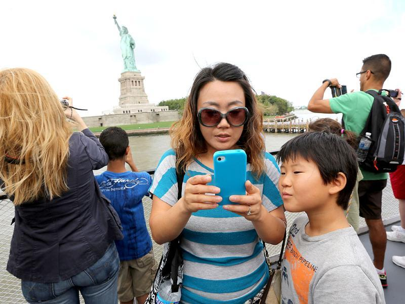 Visitors to fhe Statue of Liberty take photos as they arrive on the first tourist ferry to leave Manhattan at in New York. AP