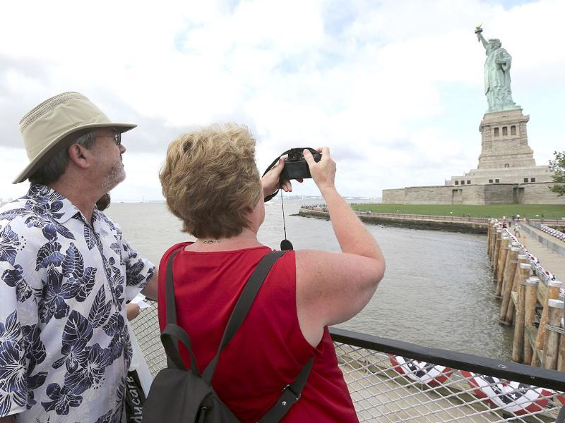 Rodney and Judy Long, of Charlotte take a photo of the Statue of Liberty as they arrive on the first tourist ferry to leave Manhattan at in New York. AP