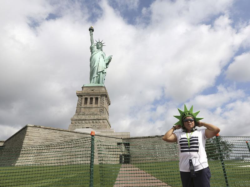 Leticia Baes poses for a photo at the bases of the Statue of Liberty at in New York. The Statue of Liberty finally reopened on the Fourth of July months after Superstorm Sandy swamped its little island in New York Harbor as Americans across the country marked the holiday with fireworks and barbecues. AP