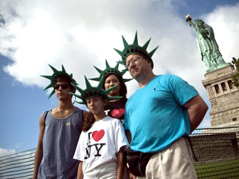 A family poses for a picture in front of the Statue of Liberty on the first day it is open to the public after Hurricane Sandy on the Liberty Island in New York City. AFP