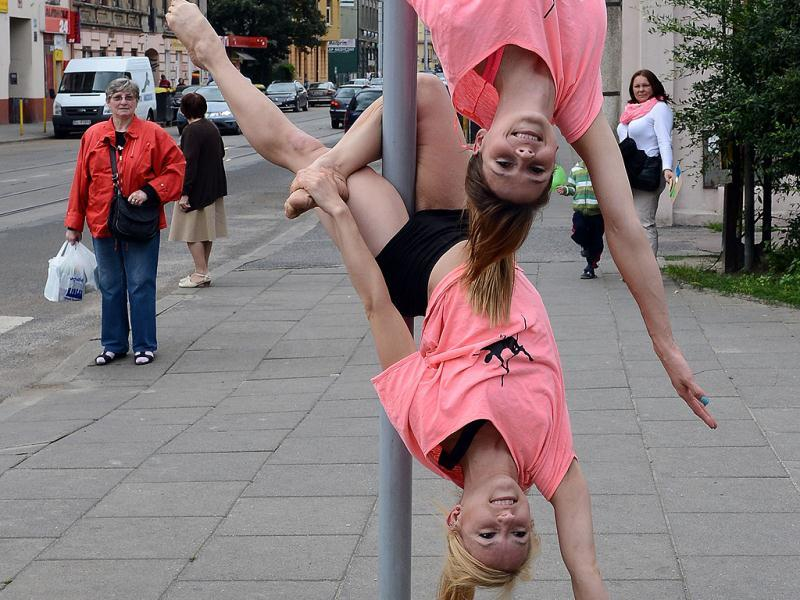 A member of the Avocadoo club performs a pole dance on a street sign pole in Lodz, central Poland. (AFP)