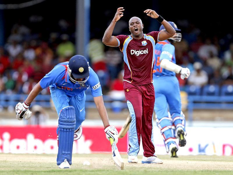 West Indies bowler Tino Best (C) reacts after the return missed the stumps and opening batsman Rohit Sharma avoids being run out during their Tri-nation series cricket match in Port-of-Spain, Trinidad. (AP)