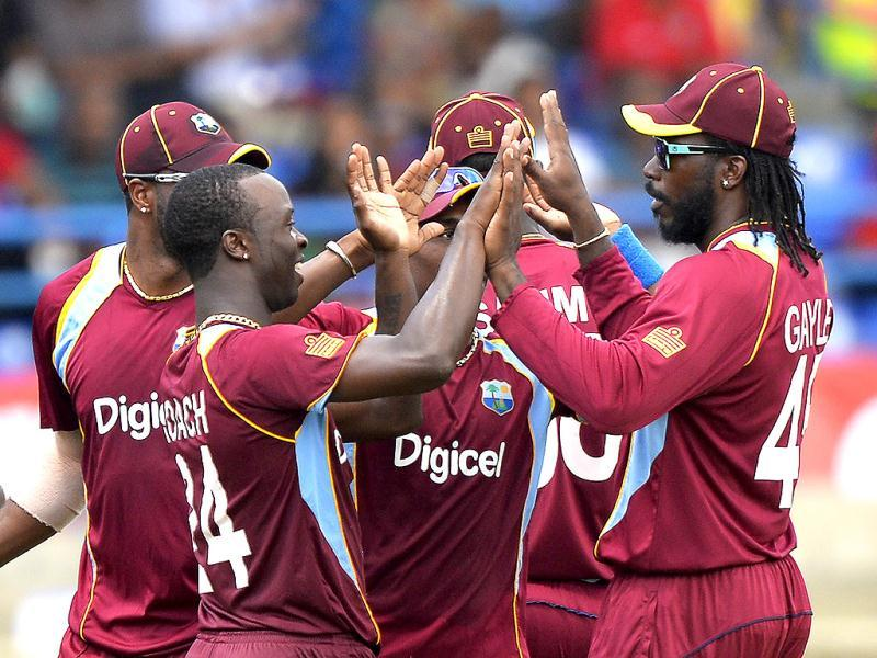 West Indies' Kemar Roach (L) celebrates with teammates after dismissing Shikhar Dhawan during the fourth match of the Tri-nation series between India and West Indies at the Queen's Park Oval in Port of Spain. (AFP)