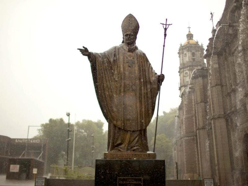A statue of Pope John Paul II stands outside the Basilica of Guadalupe during heavy rain in Mexico City. (AP)