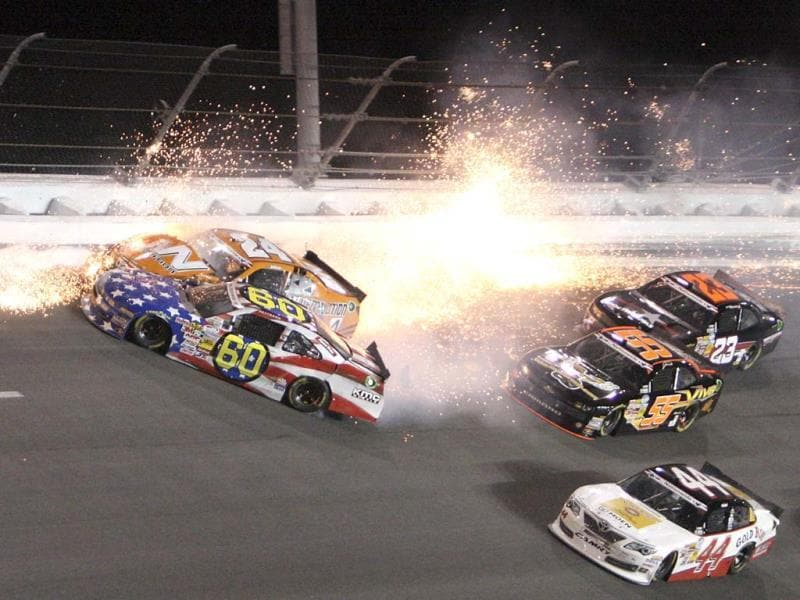 Travis Pastrana (60) crashes into Jason White (24) in turn 4 of the NASCAR Nationwide auto race at Daytona International Speedway in Florida. (AP)