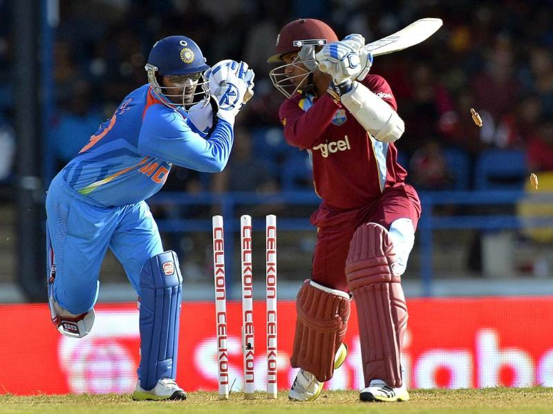Wicketkeeper Dinesh Karthik (L) unsuccessfully tries a stump-out attempt against West Indies cricketer Denesh Ramdin during the fourth match of the Tri-Nation series between India and West Indies at the Queen's Park Oval in Port of Spain. AFP Photo