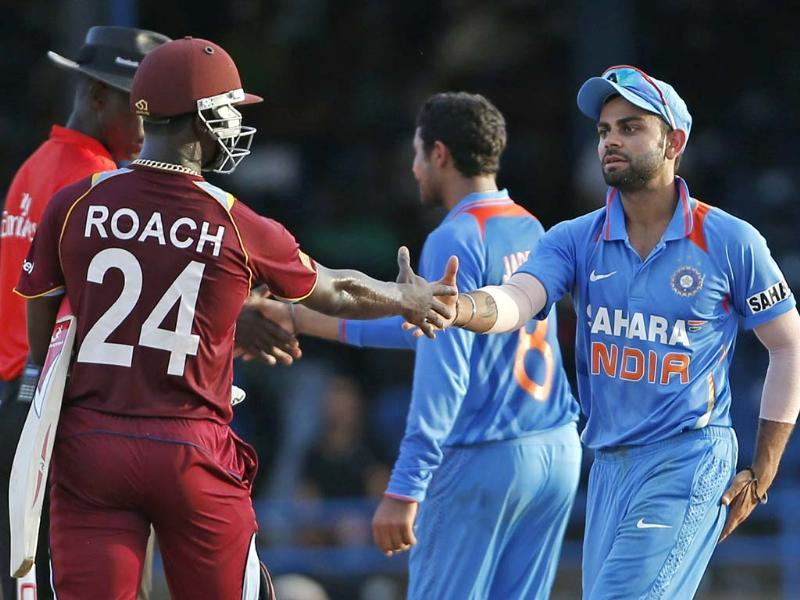 Acting captain Virat Kohli, right, shakes hands with West Indies' Kemar Roach at the end of their Tri-Nation Series cricket match in Port-of-Spain. AP Photo