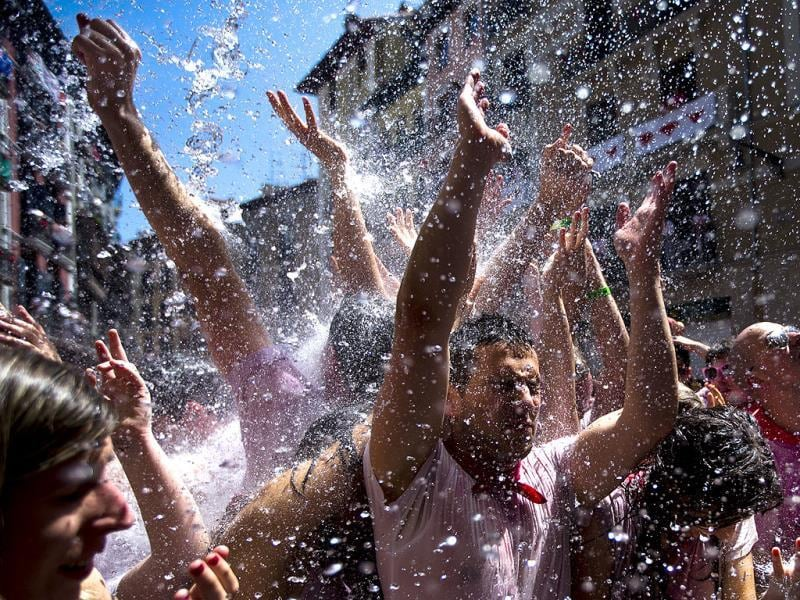 Revelers are sprayed with water thrown from balconies during the launch of the 'Chupinazo' rocket, to celebrate the official opening of the 2013 San Fermin fiestas in Pamplona, Spain. AP
