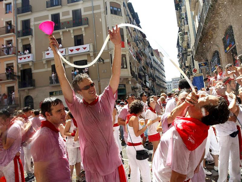 A reveller is fed alcohol through a tube at the start of the San Fermin festival in Pamplona. Reuters