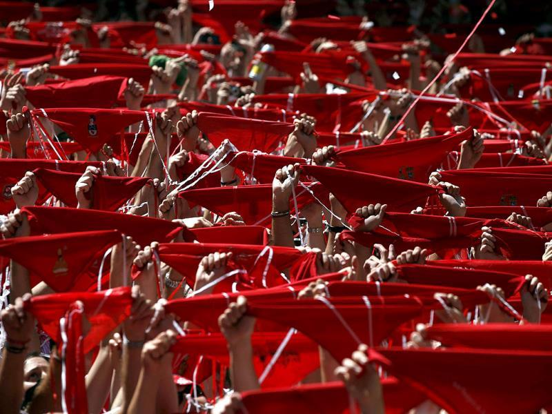 Revellers hold up their red scarves during the start of the San Fermin festival in Pamplona, Spain. Reuters