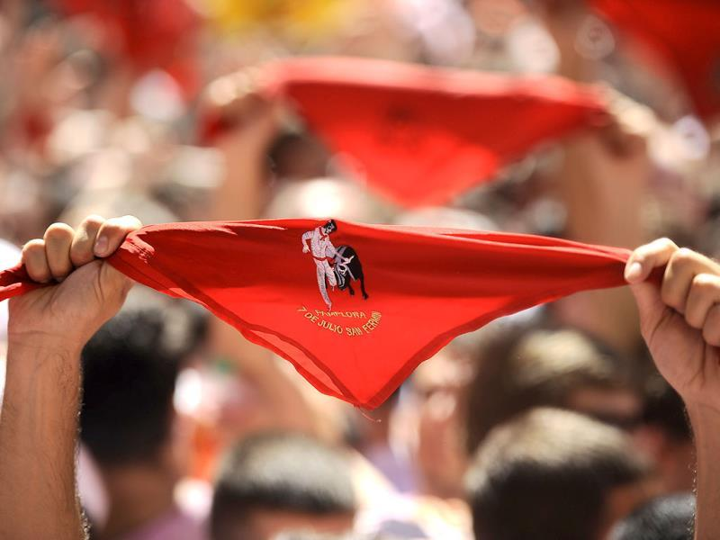 Revelers hold up traditional red neckties as tens of thousands of people packed Pamplona's main square in Pamplona, Spain during the start of the San Fermin festival. AP