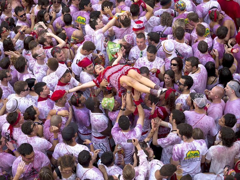 Revelers hold up a girl during the launch of the Chupinazo rocket, to celebrate the official opening of the 2013 San Fermin fiestas in Pamplona, Spain. AP