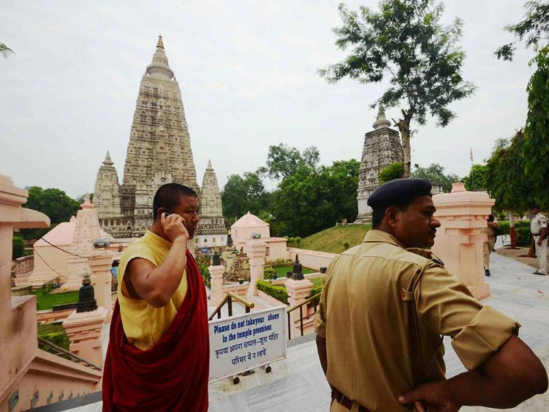 A policeman stands by as a man speaks on the phone at the Bodh Gaya Buddhist temple complex after 9 low-intensity blasts took place injuring two people. AFP