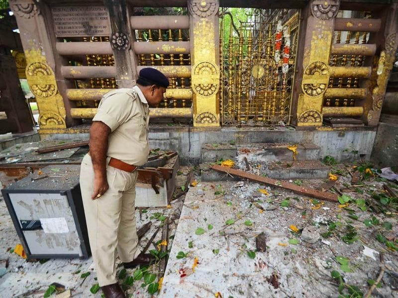 A policeman looks at debris left after 9 low-intensity blasts took place at the Bodh Gaya Buddhist temple complex in Bihar on July 7, 2013. AFP