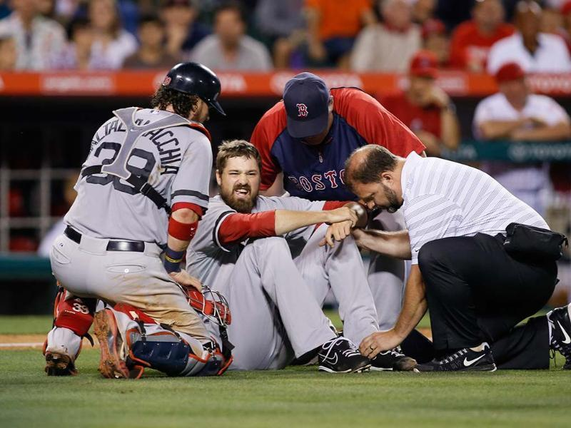 Boston Red Sox pitcher Andrew Miller is checked on by catcher Jarrod Saltalamacchia (L), manager John Farrell (top C) and a trainer after sustaining an injury against the Los Angeles Angels during the seventh inning of an MLB American League baseball game in Anaheim, California. Reuters
