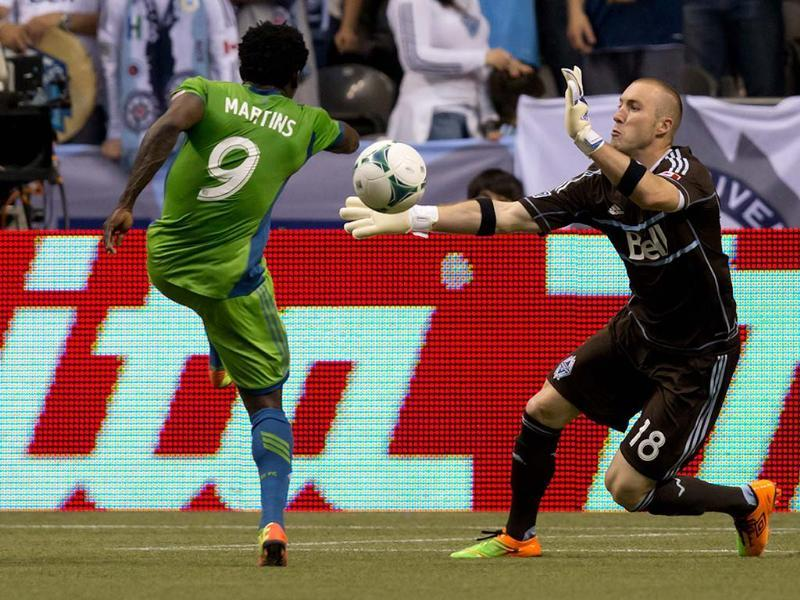 Seattle Sounders' Obafemi Martins, left, of Nigeria, is stopped by Vancouver Whitecaps' goalkeeper Brad Knighton during the first half of an MLS soccer match in Vancouver, British Columbia. AP/The Canadian Press