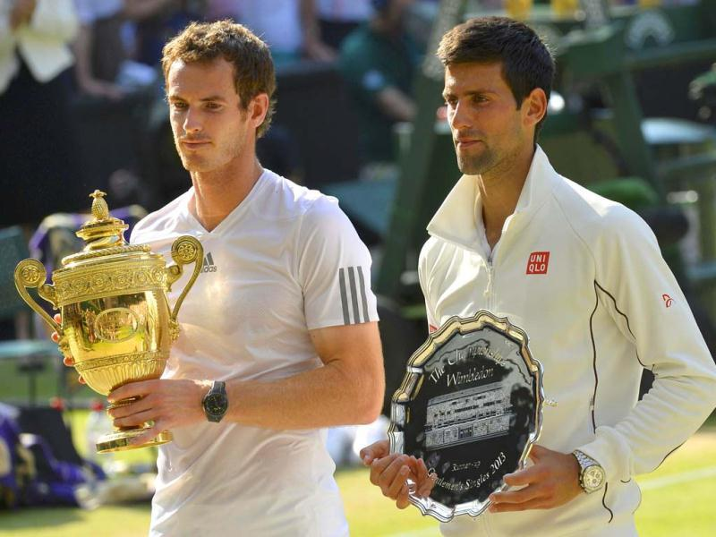 Andy Murray holds the winners trophy with Novak Djokovic holding the runners-up trophy after defeating the latter in their Wimbledon men's singles final. Reuters