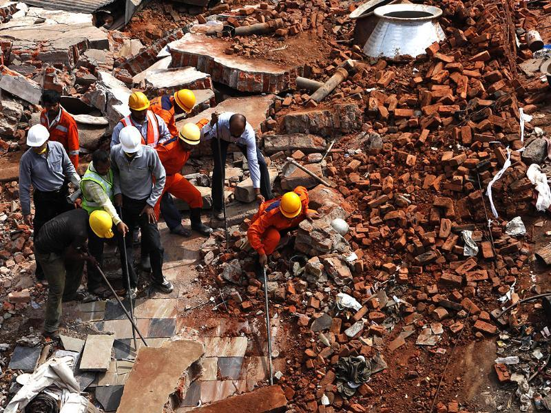 Rescue workers look for survivors from the debris of a collapsed building. (AP Photos)