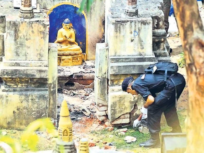 A National Security Guard (NSG) soldier collects the evidence from the site of the Mahabodhi Temple in Bodh Gaya a day after the serial blasts. (AP Photo)