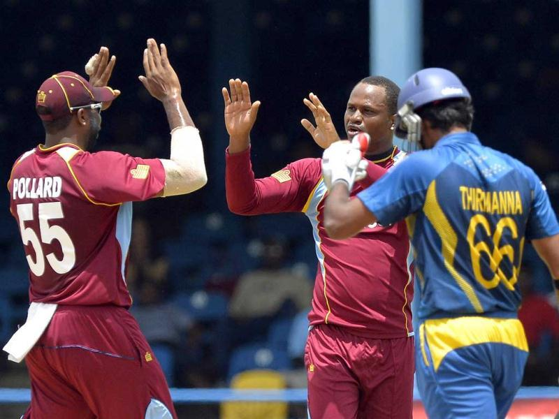 West Indies bowler Marlon Samuels (C) celebrates with team captain Kieron Pollard (L) after bowling out Sri Lankan cricketer Lahiru Thirimanne (R) during the fifth match of the Tri-Nation series between Sri Lanka and West Indies at the Queen's Park Oval stadium in Port of Spain. AFP Photo