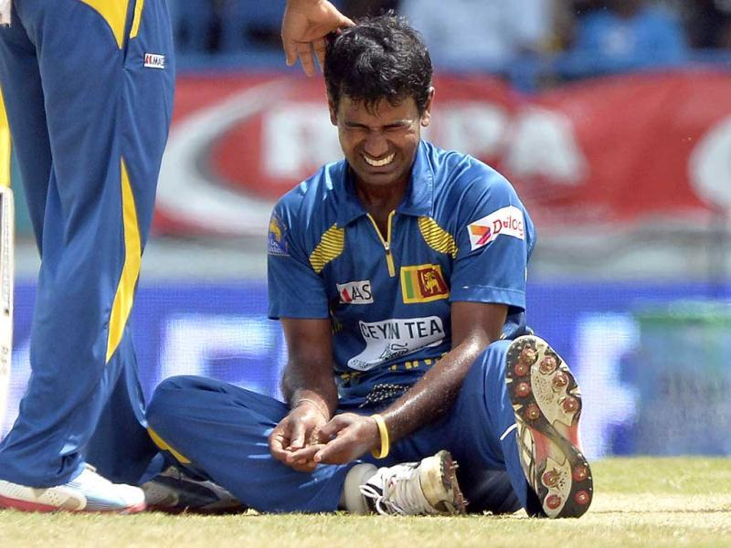 Sri Lankan bowler Nuwan Kulasekara grimaces in pain after getting a gash on the index finger of the left hand by a ball hit by West Indies batsman Chris Gayle during the fifth match of the Tri-Nation series between Sri Lanka and West Indies at the Queen's Park Oval stadium in Port of Spain. AFP Photo