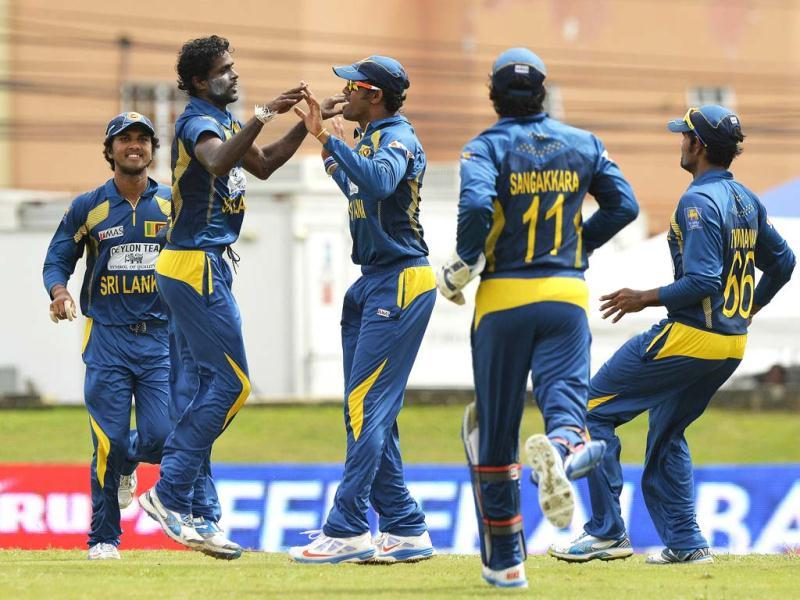 Sri Lankan cricketer Shaminda Eranga (2nd-L) celebrates with teammates after dismissing West Inides cricketer Johnson Charles during the fifth match of the Tri-Nation series between Sri Lanka and West Indies at the Queen's Park Oval stadium in Port of Spain. AFP Photo