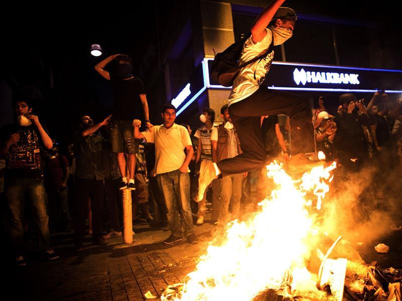 A Turkish protestor jumps over a bonfire during a protest in Istiklal avenue in Istanbul. (AFP Photo)