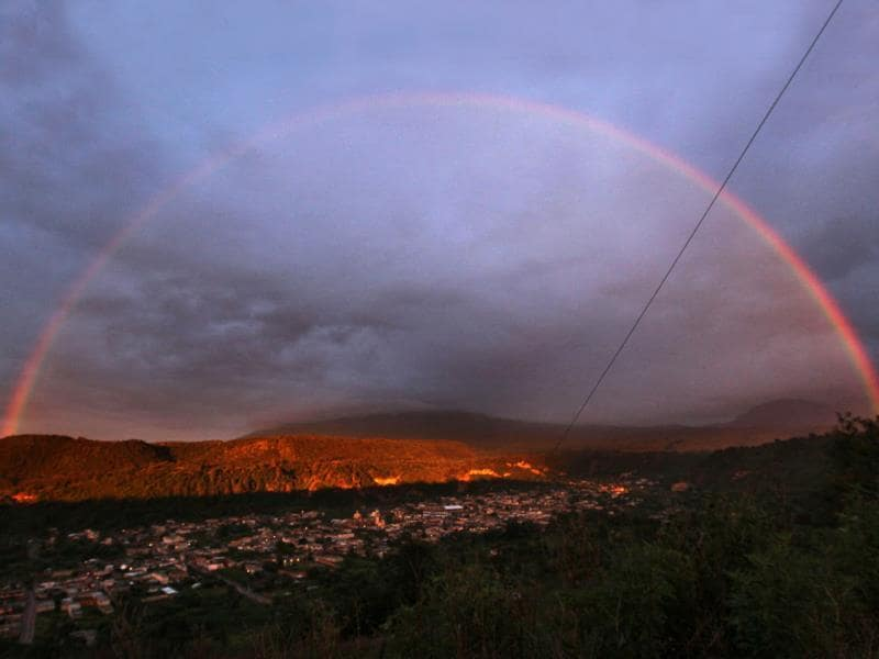A rainbow forms over the town of Santiago Xalizintla where the Popocatepetl volcano is covered by clouds in Mexico. (AP Photo)