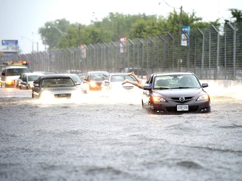 A woman gets back in her car in flood water on Lakeshore West during a storm in Toronto. (AP Photo)
