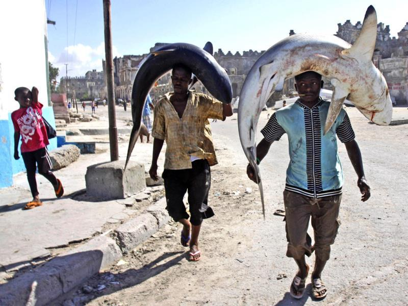 Somali fishermen carry their catch on their heads as they walk to the market in Mogadishu, Somalia. (AP Photo)