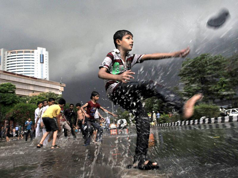 Children, breaking the cliche, instead of surrendering to the idiot box, had fun in the streets as heavy rains lashed Delhi. (HT Photo/Vipin Kumar)