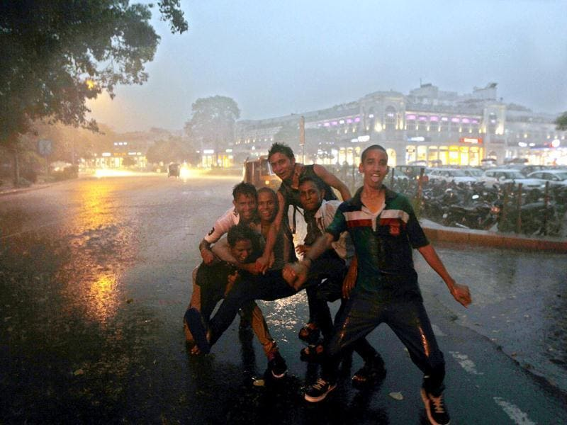 People pose enthusiastically in Connaught Place, New Delhi even when heavy rains lash the city. (HT Photo/Ajay Aggarwal)