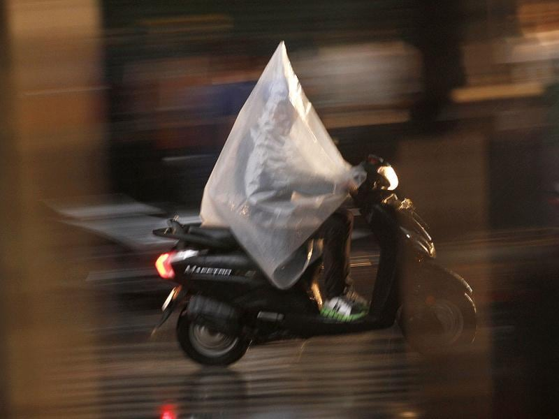 Trying to escape the rain God's fury, a man covers himself in plastic sheet as he makes his way in the rain. (HT Photo/Virendra Singh Gosain)