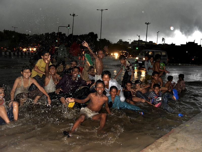 Who cares! Rain or not, we are game say these children as rains lashed the city on Tuesday evening. (HT Photo/Shubham Gupta)