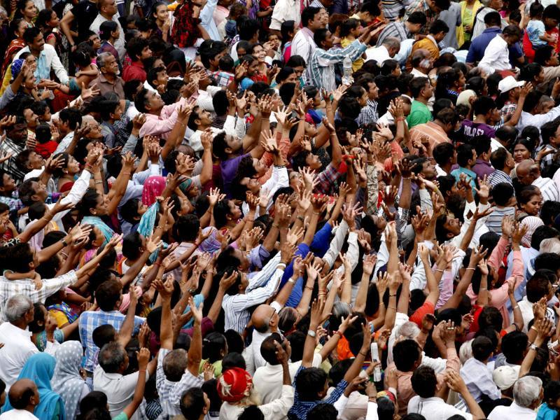 Devotees raise their hands to catch offerings during the annual chariot procession of Hindu god Lord Jagannath in Ahmadabad. AP/ Solanki