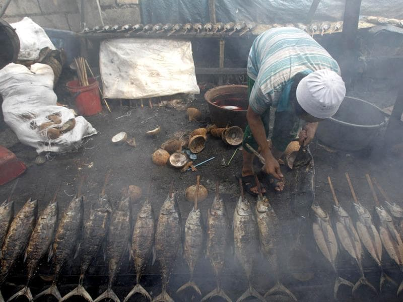 A Muslim man cooks yellow fin tuna before selling them at a market during the holy Islamic month of Ramadan in Manila July 10, 2013. REUTERS