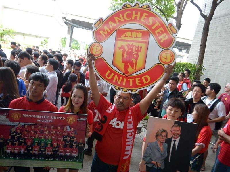 Manchester United fans hold posters as team players arrive at Don Muang International airport in Bangkok ahead of a July 13 friendly against a Thai All-Star XI as the club begins its new era under boss David Moyes. AFP